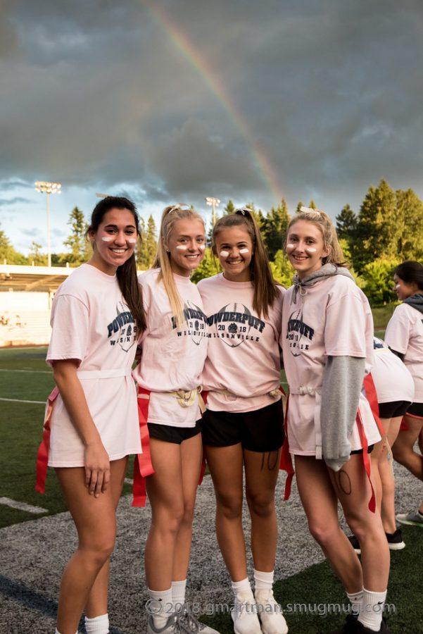 Sydney Carskadon, Lainnee Robinson, Julia Huchler, and Hannah Scott stand under a rainbow after winning the championship game.