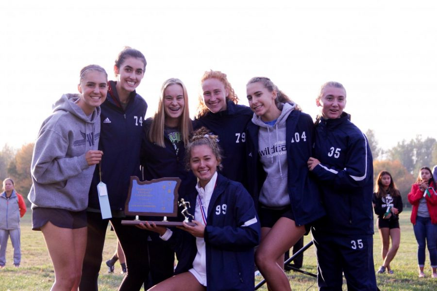 The+Wilsonville+High+School+varsity+girls+team+smile+as+they+hold+the+winning+trophy.+Both+varsity+teams+qualified+for+state.+