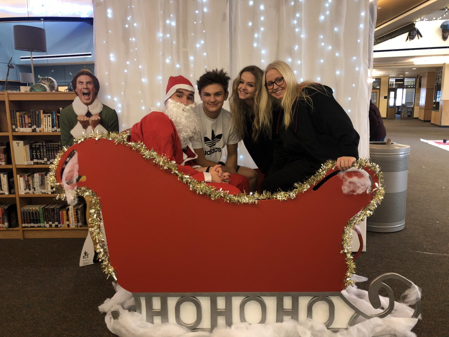 Students Chris Grizzell, Hunter Napoli, Jessica Caulk, and Mckina Stalheim pose in the custom sleigh made for the Wildcat Photo Booth. Students can take pictures in the sleigh up until Winter Break.