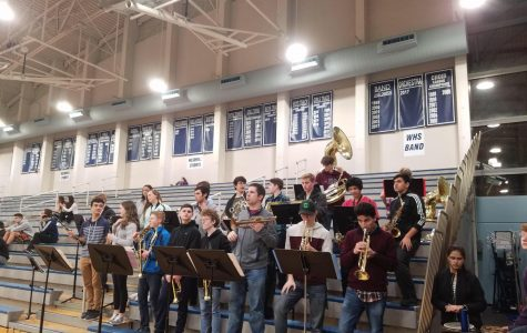 The pep band performing at a basketball game, comprised of symphonic, jazz, and concert ensemble members.