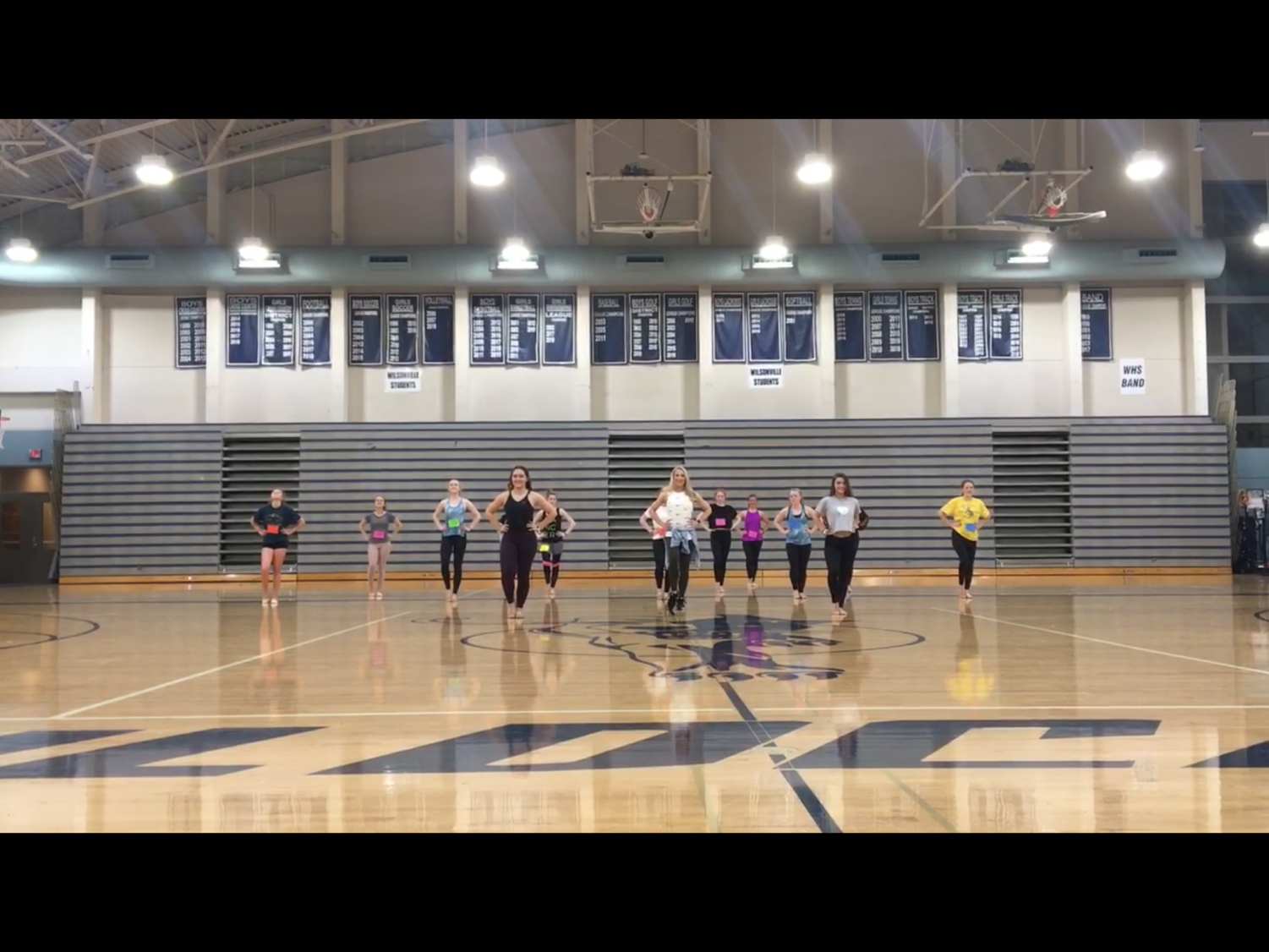 Dancers and one of the coaches  in the beginning of preforming tryout routine.