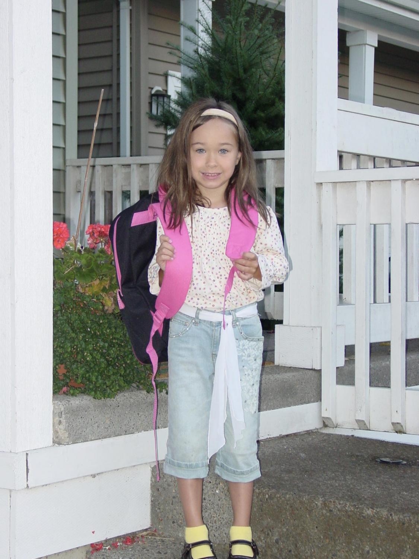 Senior+Aly+Johnston+smiles+on+her+doorstep+before+her+first+day+of+kindergarten.+Photo+credit+Aly+Johnston.
