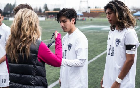 Senior defender Daniel Espinoza receives his medal after the game.