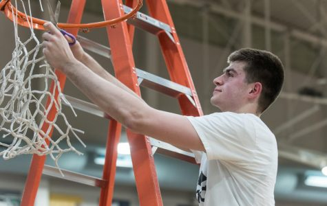Dakota Reber cuts the net after the playoff win over Corvallis.