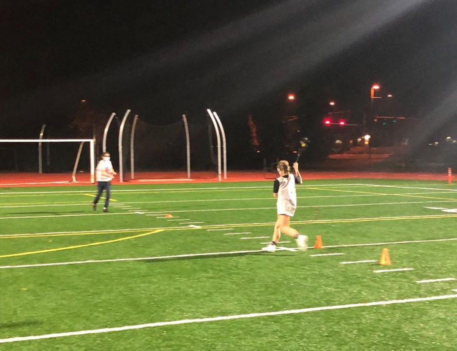 Sophomore Fiona Dunn cradles the ball as she runs towards Senior Maura Schramm, during a Covid-friendly lacrosse practice.