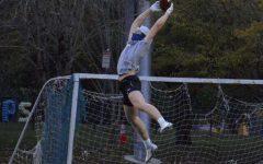 Kellen Hartford, a junior at Wilsonville High School, seen catching a football, masked up on the field. Photo belongs Ava Stenstrom.