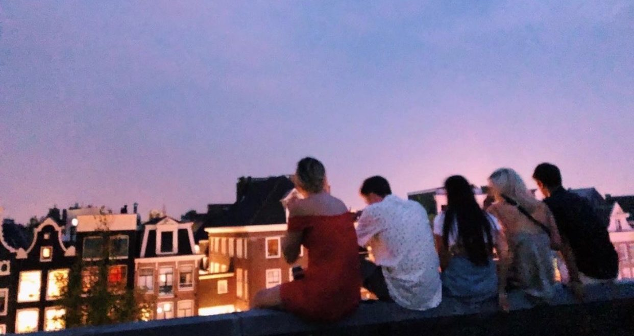 Taryn Lamb and friends  sitting on a rooftop enjoying a beautiful summer sunset in London. Some of Lambs favorite memories from Studying Abroad were nights like this out on the town.