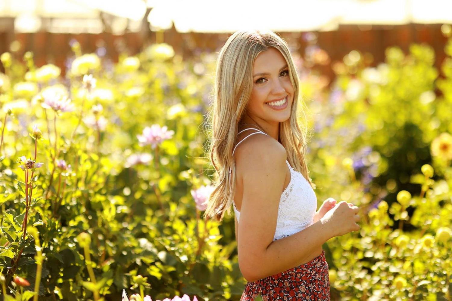 Senior, Maddy Duquette, smiling in the pretty flowers and posing for Haley Graham.