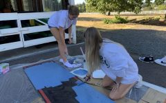 Ellie Wettstein and Piper Colby working hard to paint a sign for the senior float.