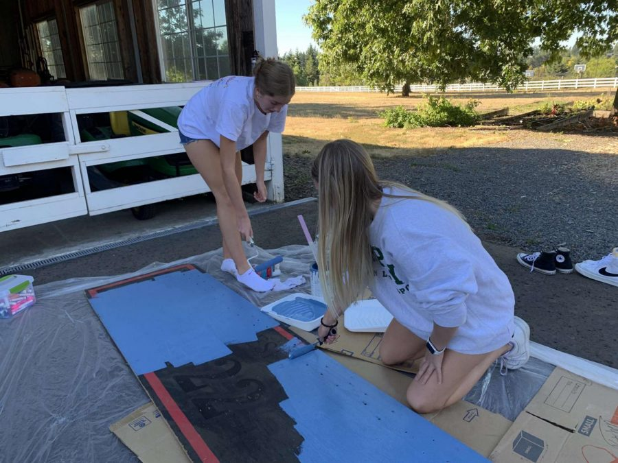 Ellie+Wettstein+and+Piper+Colby+working+hard+to+paint+a+sign+for+the+senior+float.