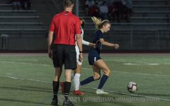 Girls soccer referee gets close to the action.