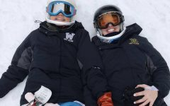 Cailin Gahan, WVHS ski team legend, smiles with a friend while laying in the snow during a practice.
