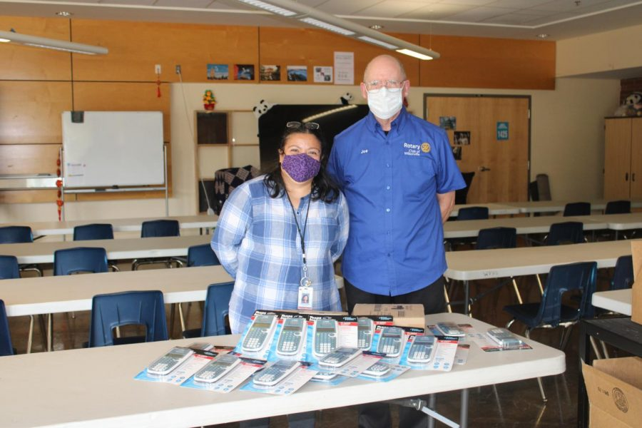 Joe from the Rotary Club of Wilsonville and Maria de Lourdes Horton of the Family Empowerment Center smile underneath their masks as they stand behind a table ladden with new calculators for the school.